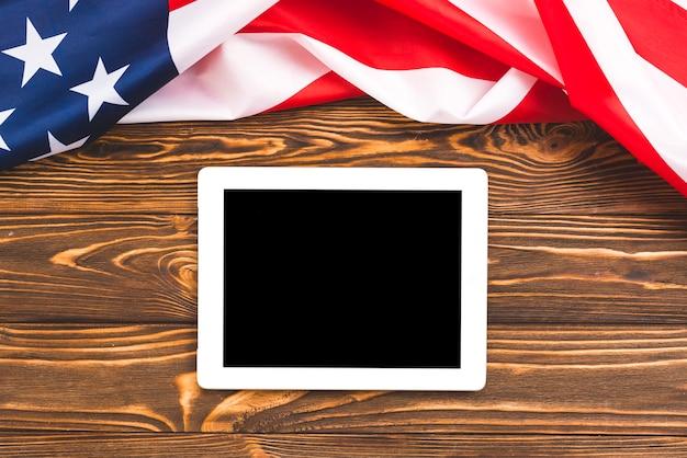 アメリカの国旗と木製の背景上のタブレットします。