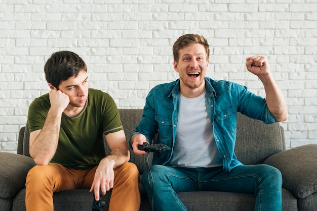 Грустный человек, смотрящий на счастливого друга, приветствующего после победы в видеоигре