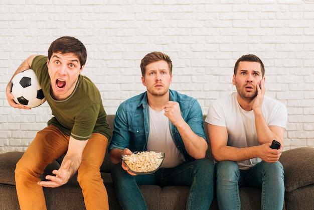 Взволнованные друзья-мужчины сидят на диване и смотрят футбольный матч по телевизору
