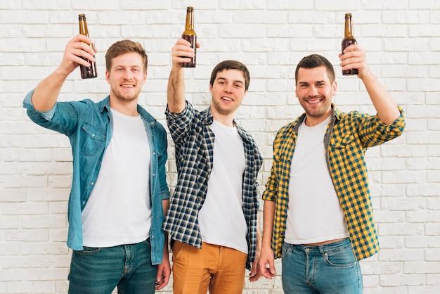 Три улыбающиеся друг друга, поднимая бутылку пива, стоящего на фоне белой кирпичной стены