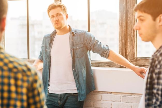 彼の友人を見て窓の近くに立っている深刻な若い男