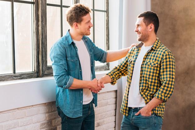 Двое молодых людей стоят возле окна и пожимают друг другу руки