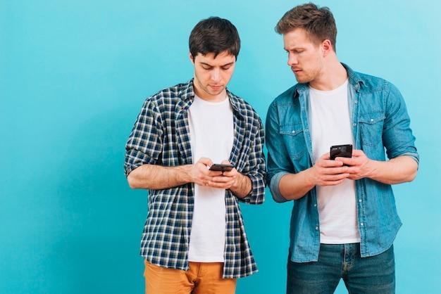 青の背景にスマートフォンで彼の友人のテキストメッセージを見ている若い男