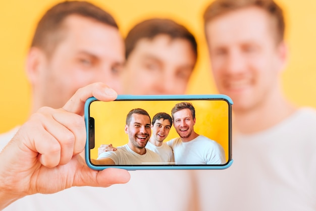 Портрет трех друзей мужского пола, принимающих селфи на смартфоне