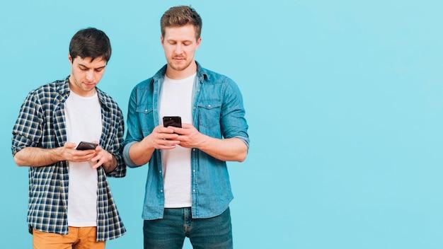 Портрет двух молодых людей, стоящих на синем фоне с помощью мобильного телефона