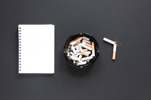 Вид сверху кучу сигарет с блокнотом