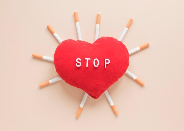 Вид сверху сердце в окружении сигарет