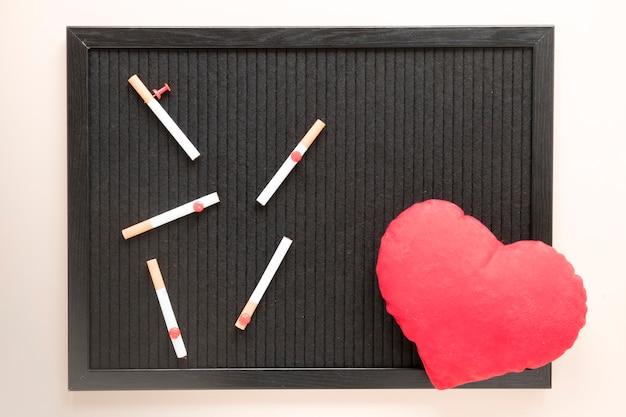 トップビューの心と黒板にタバコ