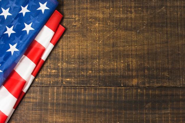 テキストを書くためのスペースを持つ木製のテクスチャ背景に折り畳まれたアメリカ国旗