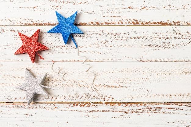 青;白の木製の織り目加工の背景に赤とスライバーの星形