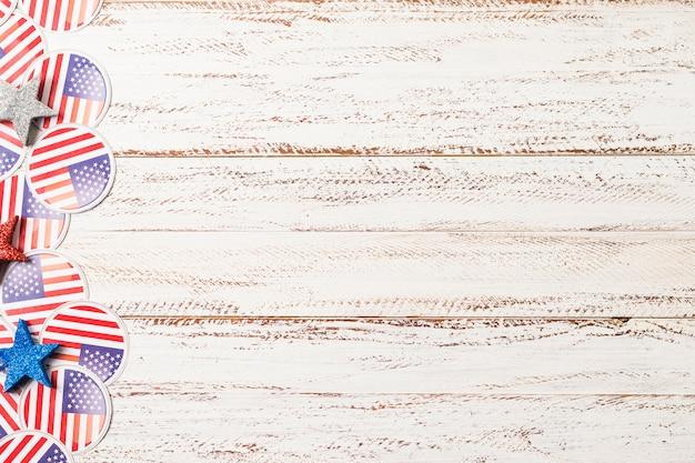 アメリカ国旗のバッジと白い木製の織り目加工の背景に星