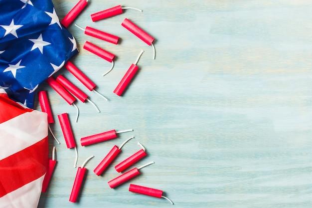 織り目加工の背景に赤の爆竹を持つアメリカのアメリカ国旗