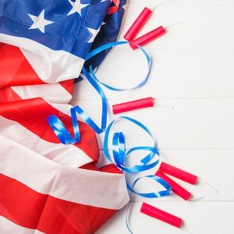 波立たせられたアメリカの国旗。青いリボンと木製のテーブルにダイナマイトの爆竹