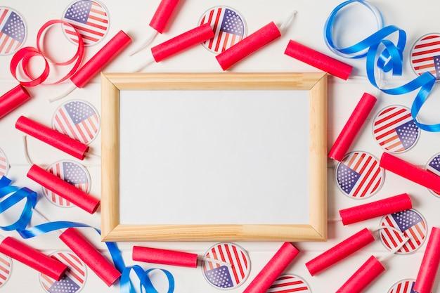 赤い爆竹空白の木製ホワイトボードの周りのリボンとアメリカの国旗バッジ