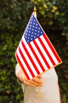 彼の顔の前でアメリカの国旗を握って男のクローズアップ