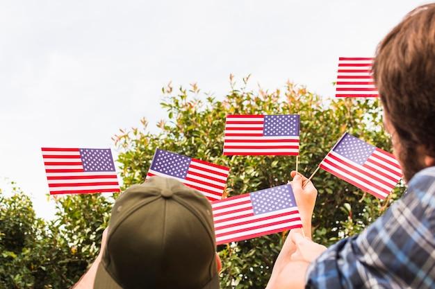 小さなアメリカの国旗を手に保持している二人の男の背面図