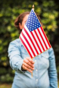 彼女の顔の前にアメリカの国旗を保持している女性のクローズアップ