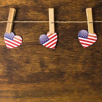 木製の机の上の物干しに掛かっている洗濯はさみを持つアメリカのハート形
