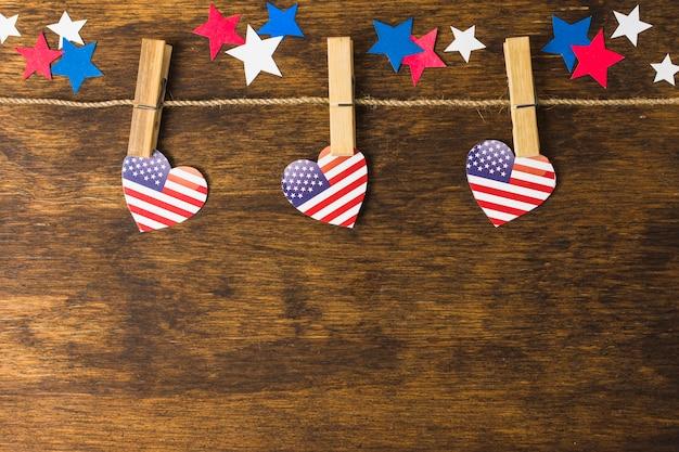 アメリカの国旗ハート形の木製の机の上の星で飾られた洗濯はさみにハングアップします。