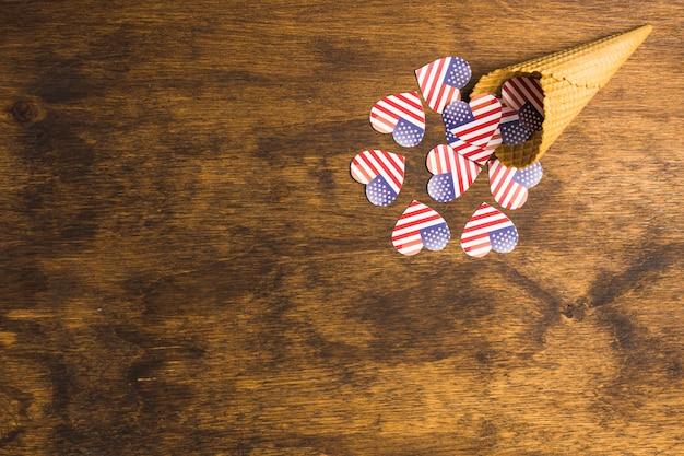 木製の机の上のワッフルコーンからこぼれたアメリカ国旗ハート形