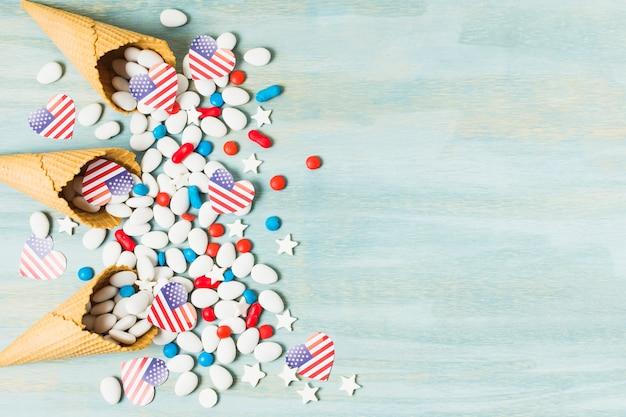 こぼれたキャンディーと青い背景にハート形のアメリカ国旗とワッフルコーンの俯瞰