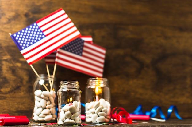 アメリカの国旗と木製の机の上の白いキャンディー瓶の中で火をつけたキャンドル