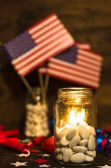 独立記念日のお祝いのためのキャンディーの瓶に燃えているキャンドル
