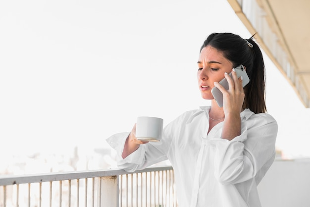 携帯電話で話しているコーヒーのカップを保持しているバルコニーに立っている若い女性