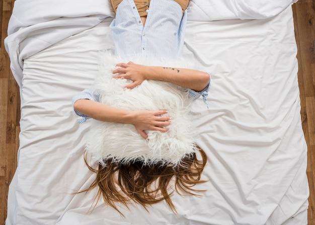 Возвышенный вид женщины, лежащей на кровати, закрывающей лицо подушкой