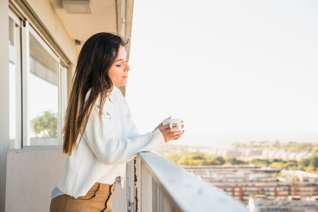 一杯のコーヒーを保持しているバルコニーに立っている若い女性