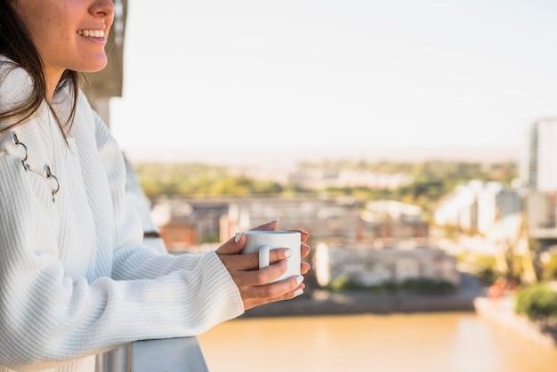 Крупный план женщины, стоящей на балконе с чашкой кофе