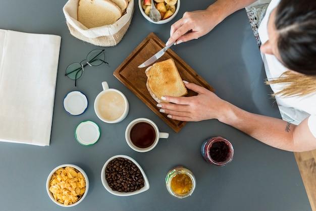 Конец-вверх женщины прикладывая варенье на хлебе над столом