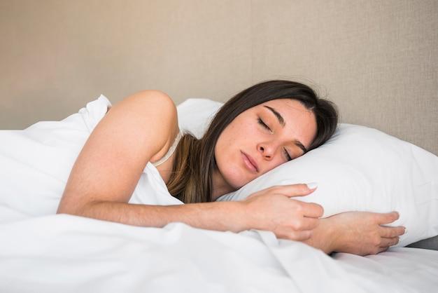 色付きの背景に対してベッドで寝ている若い女性の笑みを浮かべてください。