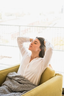肘掛け椅子に座って眠そうな疲れ若い女性の背面図