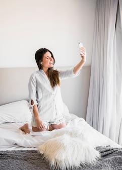 Улыбается портрет молодой женщины на коленях на кровати, принимая селфи по мобильному телефону