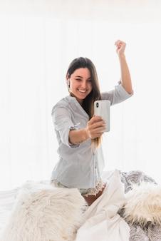 Молодая женщина делает видео звонок на смартфоне танцы