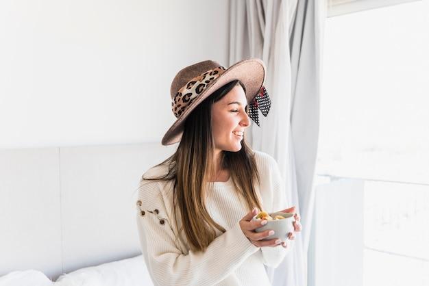 朝のフルーツサラダのボウルを楽しんでいる若い女性の肖像画を笑顔