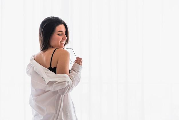 カーテンの前に立っている笑顔の美しい若い女性