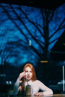 カフェでスムージーの瓶を持つ若い女性の肖像画
