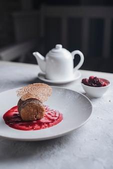 Декоративный десерт с соусом из красных ягод на белой керамической тарелке