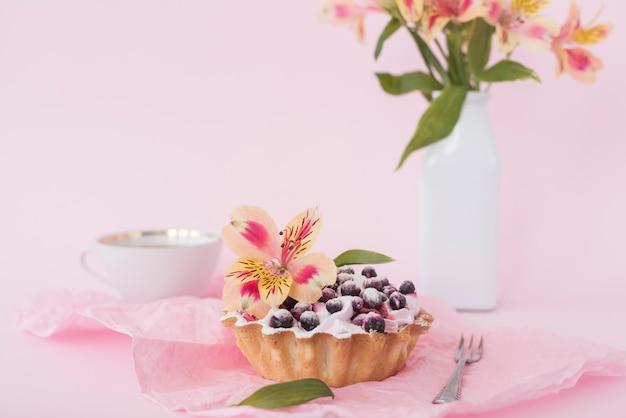 ピンクの背景に対してアルストロメリアの花で飾られたブルーベリーのタルト