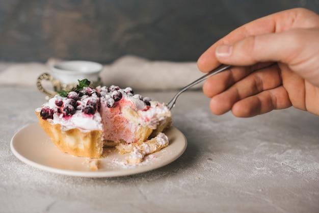 Крупный план человека, едящего пирог с вилкой