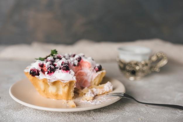 ステンレス製のフォークでセラミックプレートの果実のタルトを食べる