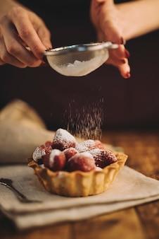 イチゴのタルトに砂糖の粉を散布する女性のクローズアップ