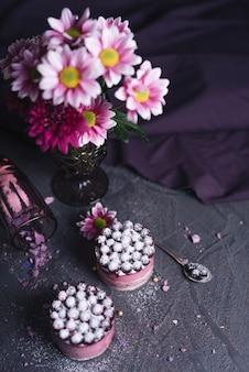 黒の織り目加工の背景においしいチーズブラックカラントケーキと花瓶の俯瞰