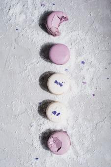 コンクリートの背景に乾燥ココナッツをまぶした紫と白のマカロン