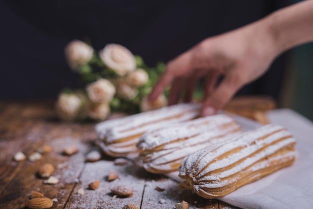 木製のテーブルにアーモンド焼きエクレアを持つ女性の手のクローズアップ