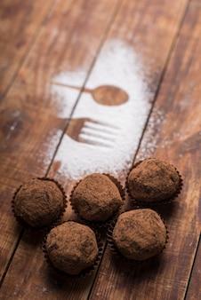 シュガーパウダーのスプーンとフォークの形の近くのココアパウダーと自家製チョコレートトリュフキャンディー