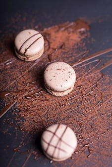 チョコレートの粉と黒の背景にマカロンの上のシロップ