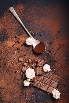 チョコレートバーとシロップの濃い色の背景にピンクのバラ